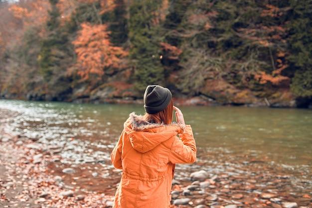 Vrolijke vrouw toerist in een jas herfst bos rivier natuur