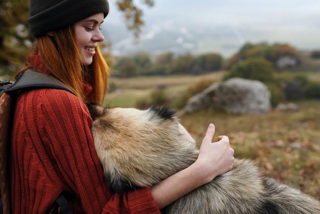 Vrolijke vrouw toerist spelen met hond natuur frisse lucht