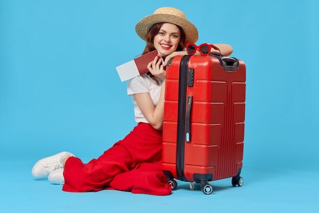 Vrolijke vrouw toeristische rode koffer passagiersluchthaven vluchtdocumenten. hoge kwaliteit foto