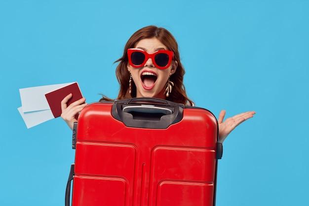 Vrolijke vrouw toeristische rode koffer passagiersluchthaven vluchtdocumenten