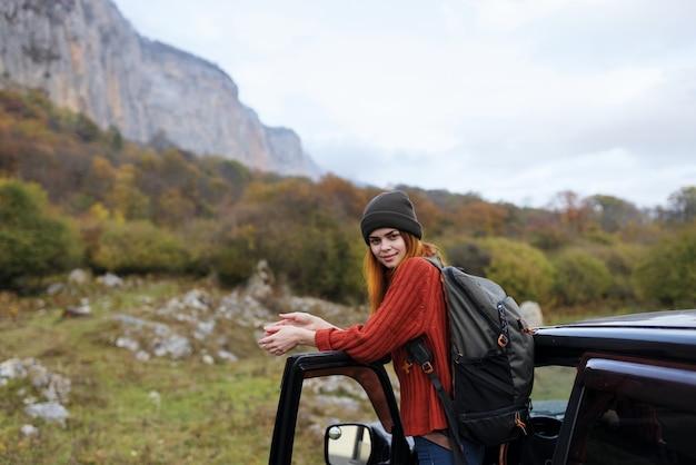 Vrolijke vrouw toeristische rugzak reizen auto reis bergen landschap