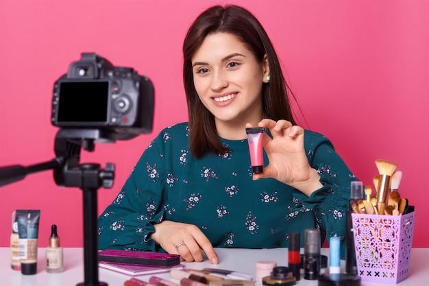 Vrolijke vrouw toont cosmetica producten tijdens het opnemen van video en het geven van adviezen