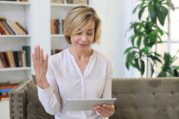 Vrolijke vrouw van middelbare leeftijd die op de bank zit, computertablet-apps gebruikt, naar het scherm kijkt, goed nieuws leest in een sociaal netwerk, online winkelt of chat.