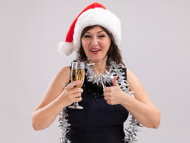 Vrolijke vrouw van middelbare leeftijd met een kerstmuts en een klatergoudslinger om de nek die een glas champagne vasthoudt en naar een camera kijkt die duim omhoog laat zien geïsoleerd op een witte achtergrond