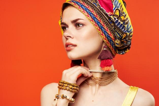 Vrolijke vrouw veelkleurige sjaal etniciteit afrikaanse stijl decoraties rode achtergrond