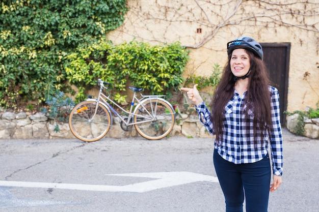 Vrolijke vrouw vertegenwoordigt een fiets op de muursteeg