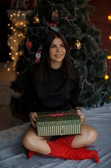 Vrolijke vrouw voor de kerstboom met het binnenkort te openen geschenk in handen kijkt vooruit en droomt van iets