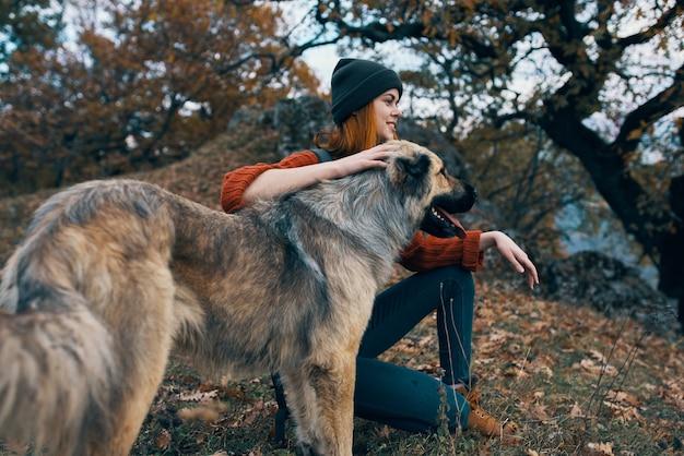Vrolijke vrouw wandelaar knuffelen hond buitenshuis reizen vriendschap