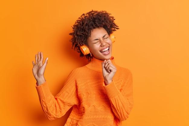 Vrolijke vrouw zingt lied houdt hand in de buurt van mond alsof de microfoon naar favoriete afspeellijst luistert via koptelefoon, nonchalant gekleed poseert tegen de levendige oranje studiomuur