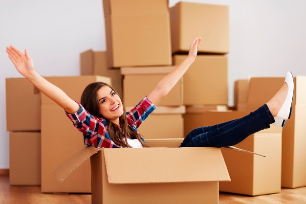 Vrolijke vrouw zitten in een kartonnen doos