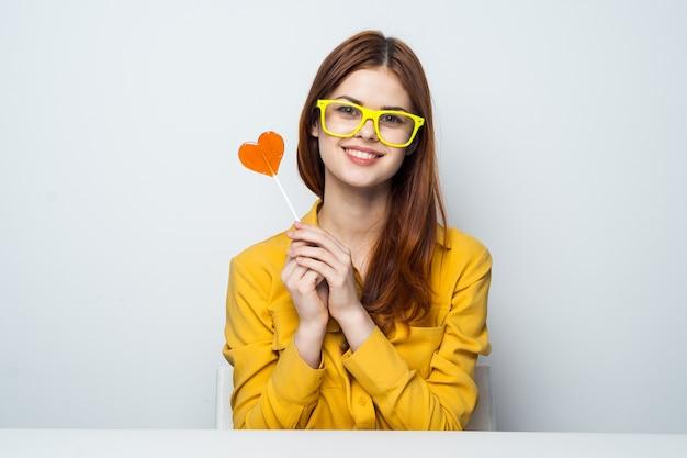 Vrolijke vrouw zittend aan de tafel stick met hart geel shirt.