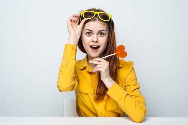 Vrolijke vrouw zittend aan de tafel stick met hart gele bril.