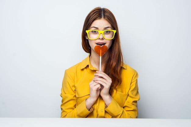 Vrolijke vrouw zittend aan de tafel stok met hart geel shirt