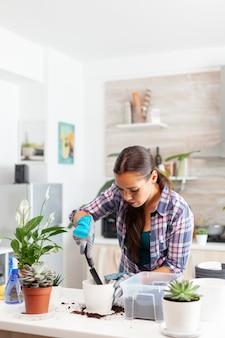 Vrolijke vrouw zorgt voor huisbloemen zittend in de keuken op tafel. bloemist herplant bloemen in witte keramische pot met schop, handschoenen, vruchtbare grond en bloemen voor huisdecoratie.