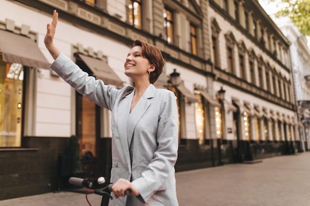 Vrolijke vrouw zwaait met haar hand in begroeting tijdens het wandelen. mooi meisje in grijs pak elektrische scooter rijden en buiten glimlachen