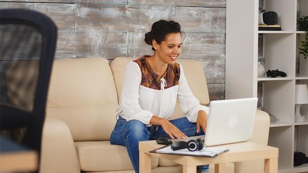 Vrolijke vrouw zwaait tijdens een videogesprek terwijl ze vanuit huis werkt.