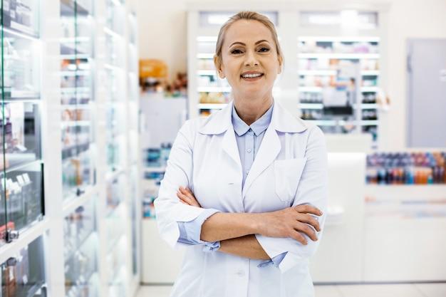 Vrolijke vrouwelijke apotheker handen kruisen en poseren op onscherpe achtergrond