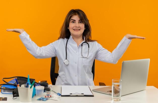 Vrolijke vrouwelijke arts van middelbare leeftijd die medische mantel en stethoscoop draagt ?? die aan bureau zit met het klembord van medische hulpmiddelen en laptop die lege geïsoleerde handen toont