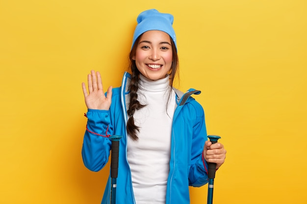 Vrolijke vrouwelijke asain-reiziger houdt wandeluitrusting vast, golven palm, begroet vriend in de bergen, is actieve wandelaar, lacht aangenaam, geïsoleerd over gele muur