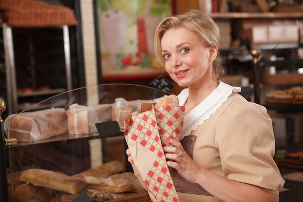 Vrolijke vrouwelijke bakker glimlachend naar de camera, werkend in haar bakkerij