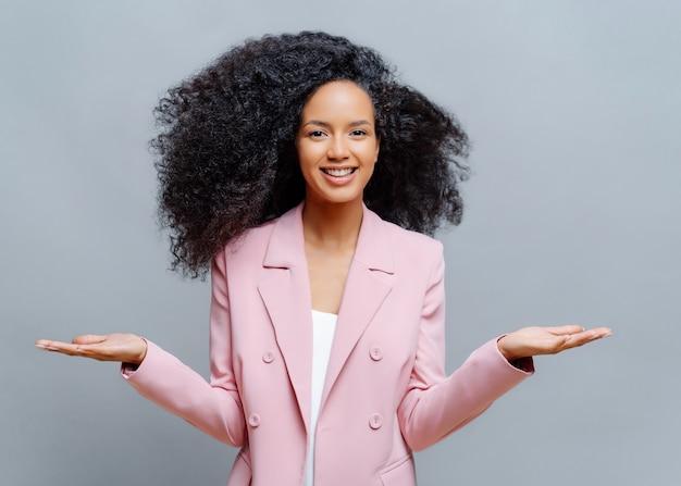 Vrolijke vrouwelijke bedrijfsmedewerker met afro-kapsel, draagt een elegant formeel violet jasje, heft beide handpalmen op, presenteert een product