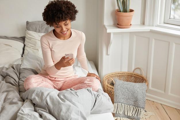 Vrolijke vrouwelijke blogger geniet van recreatietijd, winkelt online, gebruikt een mobiele telefoontoepassing