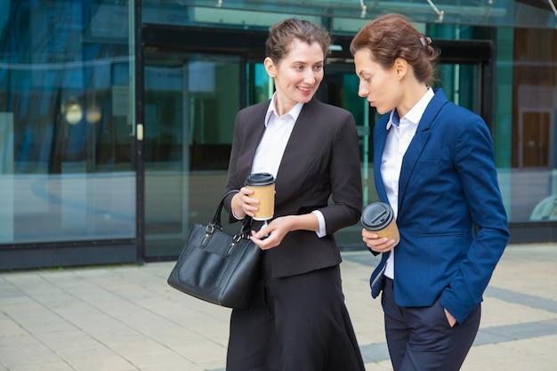 Vrolijke vrouwelijke collega's buiten koffie drinken, glimlachen, lachen. jonge onderneemsters die kostuums dragen, die samen in stad lopen. werk pauze concept