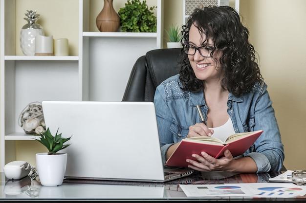 Vrolijke vrouwelijke freelancer maken van aantekeningen
