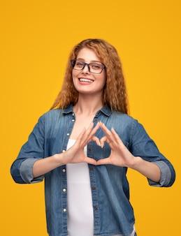 Vrolijke vrouwelijke gebaren hart en glimlachen