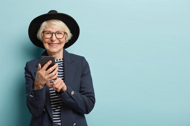 Vrolijke vrouwelijke gepensioneerde m / v leert hoe te gebruiken smartphone, melding typen