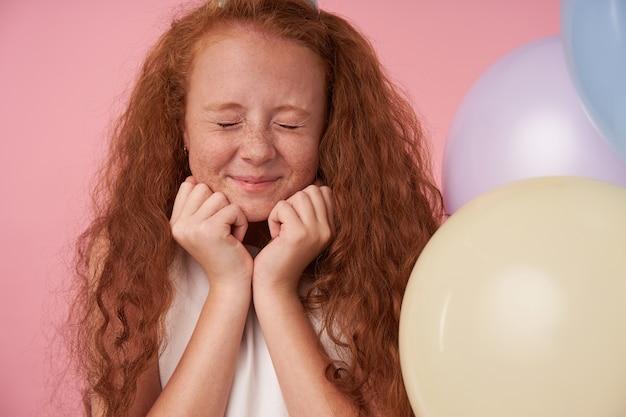 Vrolijke vrouwelijke jongen met foxy lang haar in feestelijke kleding poseren op roze achtergrond met gesloten ogen, drukt ware positieve emoties uit en houdt handen onder de kin. kinderen en viering concept