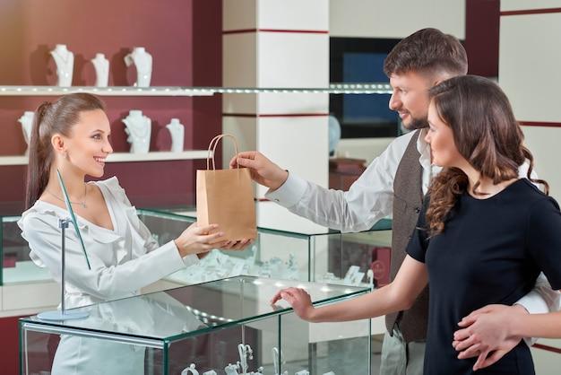 Vrolijke vrouwelijke juwelier die aankoop in een boodschappentas overhandigt aan hij