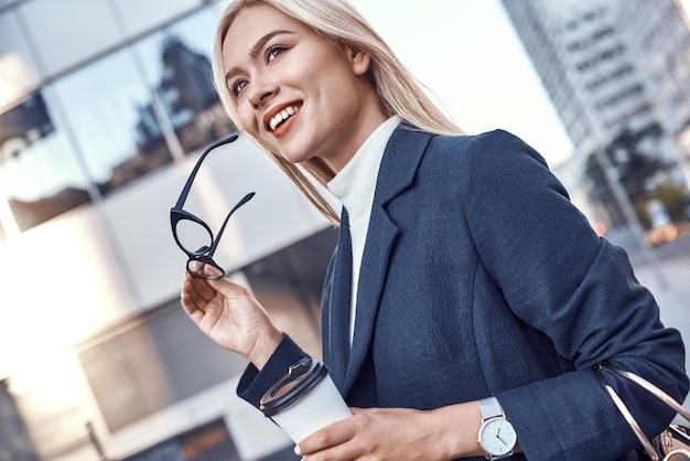 Vrolijke vrouwelijke manager die 's ochtends te voet aan het werk gaat Premium Foto