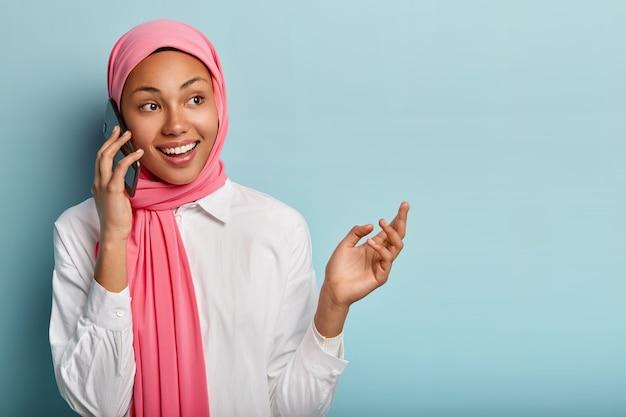 Vrolijke vrouwelijke model bespreekt geweldig nieuws met goede vriend, smartphone in de buurt van oor houdt, ziet er vrolijk uit