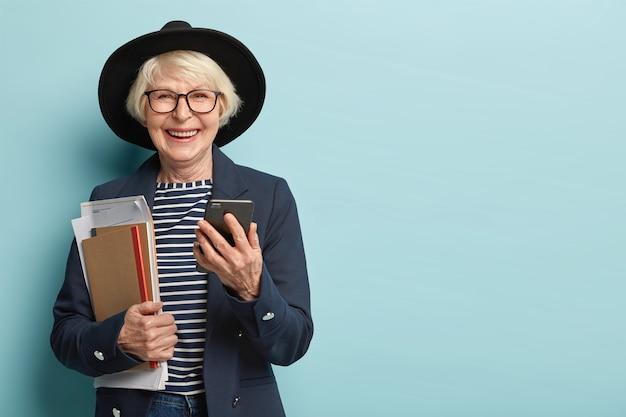 Vrolijke vrouwelijke moderator socialiseert online, houdt moderne gadget vast, ontvangt melding, houdt papieren met notitieblok, gekleed in stijlvolle formele kleding, geïsoleerd over blauwe muur, lege ruimte