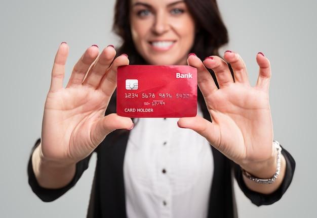 Vrolijke vrouwelijke ondernemer die en rode creditcard glimlacht aantoont