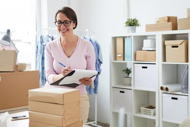 Vrolijke vrouwelijke online winkelmanager die lijst met bestellingen maakt