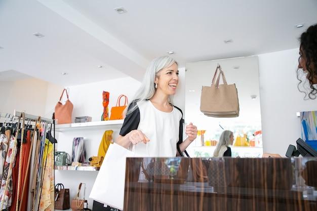 Vrolijke vrouwelijke shopper met papieren zakken en glimlachend bij kassier of verkoper in mode winkel. vrouw die aankoop neemt en winkel verlaat. gemiddeld schot. winkelen concept