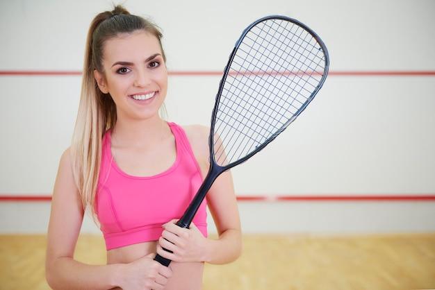Vrolijke vrouwelijke squashspeler met racket