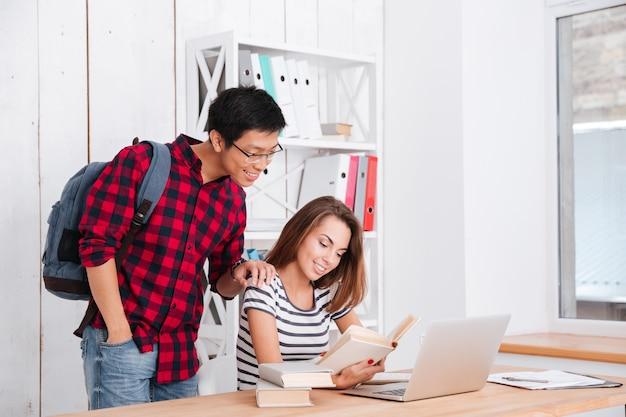 Vrolijke vrouwelijke student die een pagina van boek leest. jongen staat in de buurt van meisje en houdt rugzak vast terwijl hij op boek kijkt en glimlacht