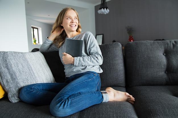 Vrolijke vrouwelijke student gedaan met haar huisopdracht