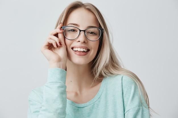 Vrolijke vrouwelijke student in stijlvolle brillen verheugt zich met succes voor examens, blij met een ontmoeting met groepsgenoten. opgetogen mooie tevreden vrouw heeft een aantrekkelijke uitstraling, vormt binnenshuis.