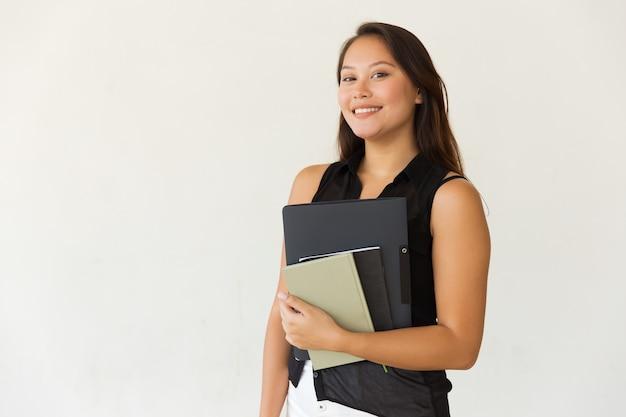 Vrolijke vrouwelijke student met map en handboeken