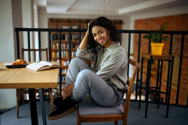 Vrolijke vrouwelijke student zit aan de tafel in het café van de bibliotheek. vrouw die een onderwerp, onderwijs en kennis leert. meisje studeert in campuscafetaria