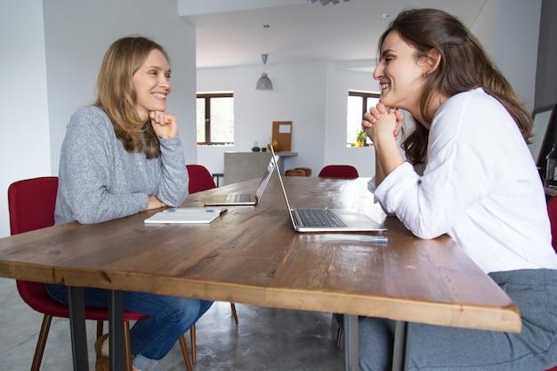Vrolijke vrouwelijke studenten chatten
