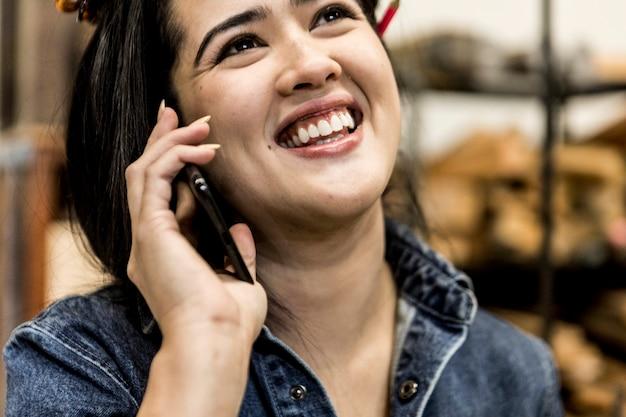 Vrolijke vrouwelijke timmerman praten aan een telefoon