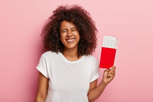 Vrolijke vrouwelijke toerist heeft plezier voor de reis, houdt instapkaartjes in het paspoort, voelt zich opgewonden over de reis, glimlacht positief, draagt een casual outfit, geïsoleerd op een roze muur, wacht op de vlucht