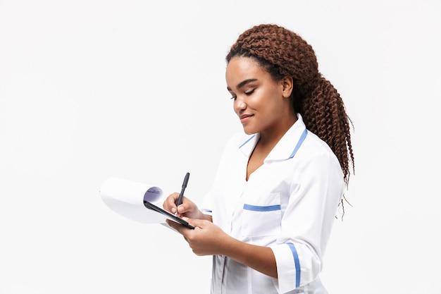 Vrolijke vrouwelijke verpleegster die medisch casusrapport schrijft dat tegen een witte muur wordt geïsoleerd