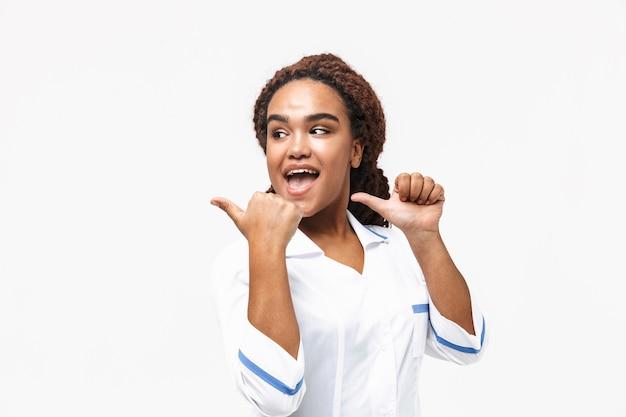 Vrolijke, vrouwelijke verpleegster, glimlachend, en, wijzende, vingers, op, copyspace, geïsoleerde, tegen, witte muur