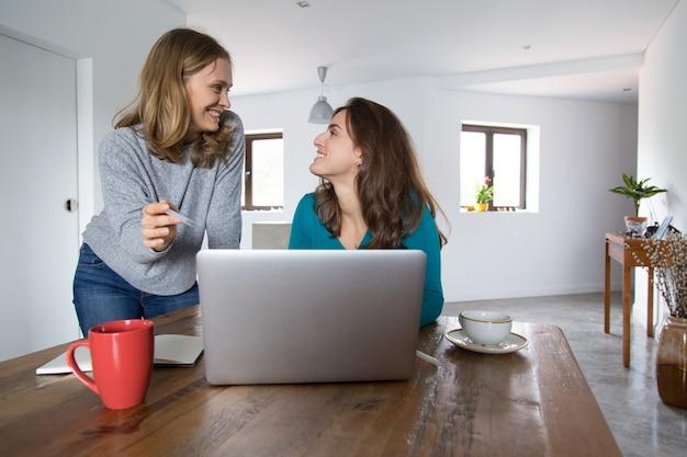Vrolijke vrouwelijke vrienden die en inhoud op media letten bespreken